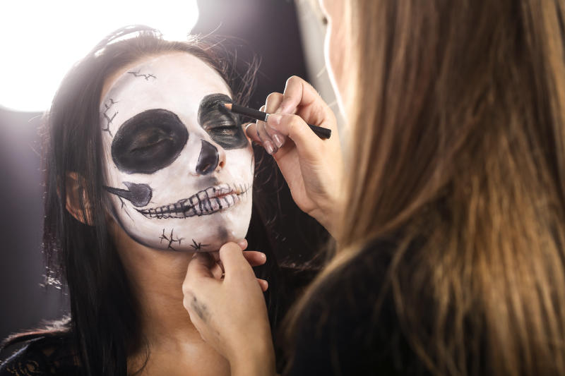 Make-up artist doing stage make-up (sugar skull body paint) with a beautiful young woman. About 25 years old Caucasian brunette.