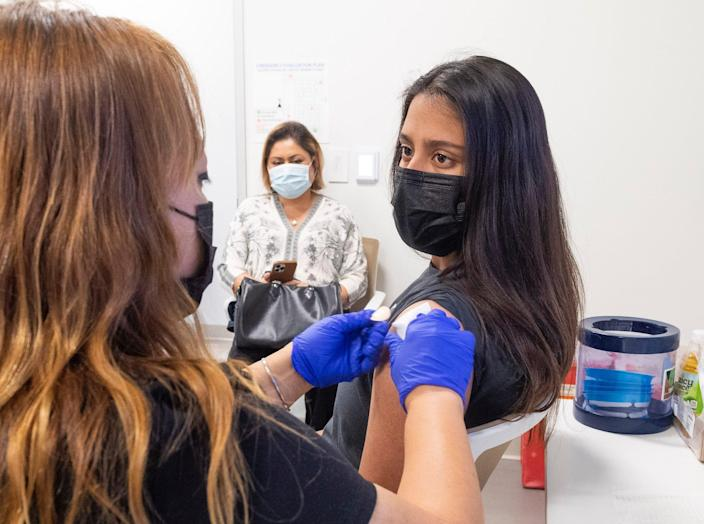 A 16-year-old getting her Pfizer-BioNTech COVID-19 vaccine