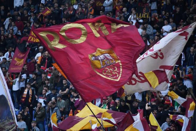 FILE PHOTO: AS Roma fans wave flags at a match against Napoli