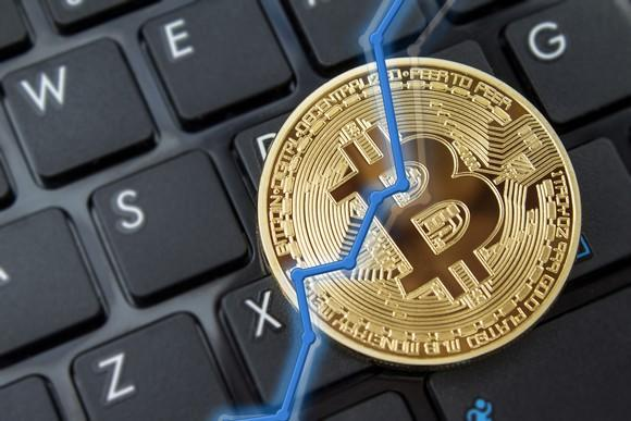 A rising chart overlaid on a physical gold bitcoin, with a keyboard in the background.