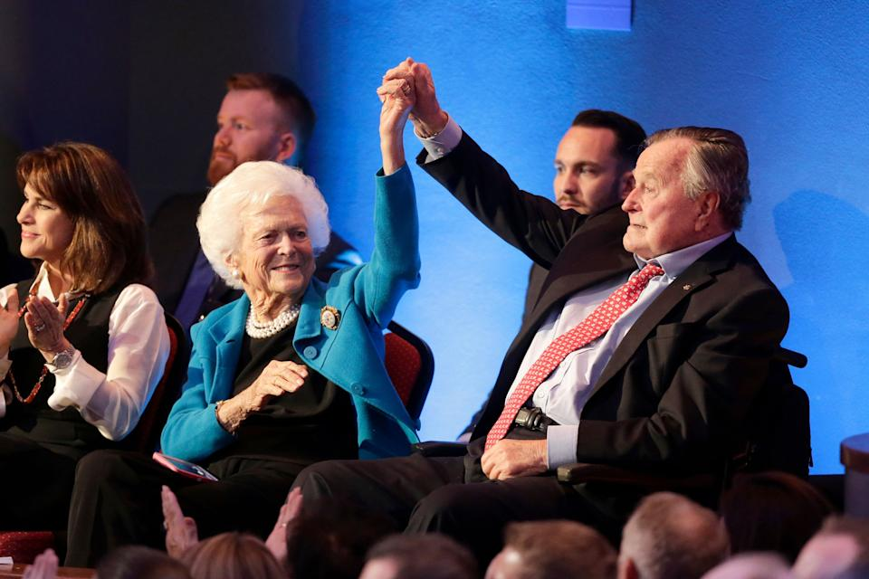 Barbara and George H.W. Bush hold up their hands at the Republican presidential primary debate sponsored by CNN and Telemundo at the University of Houston on Feb. 25, 2016.