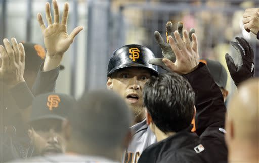 Hunter Pence is congratulated by San Francisco Giants teammates after his solo home run against the Los Angeles Dodgers in the inning of a baseball game in Los Angeles Wednesday, April 3, 2013. (AP Photo/Reed Saxon)