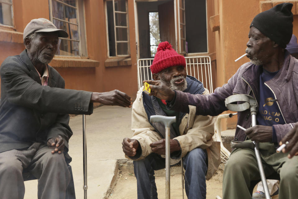Elderly men share a light moment while smoking at Melfort Old People's home on the outskirts of Harare, Zimbabwe, Sunday, July 25, 2021. The economic ravages of COVID-19 are forcing some families in Zimbabwe to abandon the age old tradition of taking care of the elderly. Zimbabwe's care homes have experienced a 60% increase in admissions since the outbreak of the pandemic in March last year. (AP Photo/Tsvangirayi Mukwazhi)