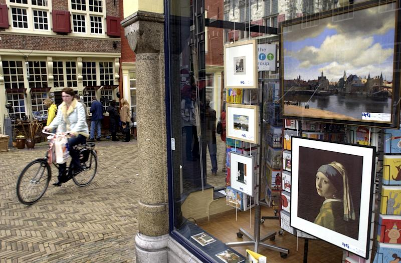 "FILE-  This May 2, 2004 file photo shows a woman passing by reproductions of Johannes Vermeer paintings, ""The Girl with the Pearl Earring"" and ""View of Delft,"" for sale in downtown Delft. You don't have to be in Delft long to see what inspired Johannes Vermeer. Meandering up and down countless bridges that stretch over canals, and past storefronts and slender houses, the quaint Dutch life sets in.     (AP Photo/Dusan Vranic, FILE)"
