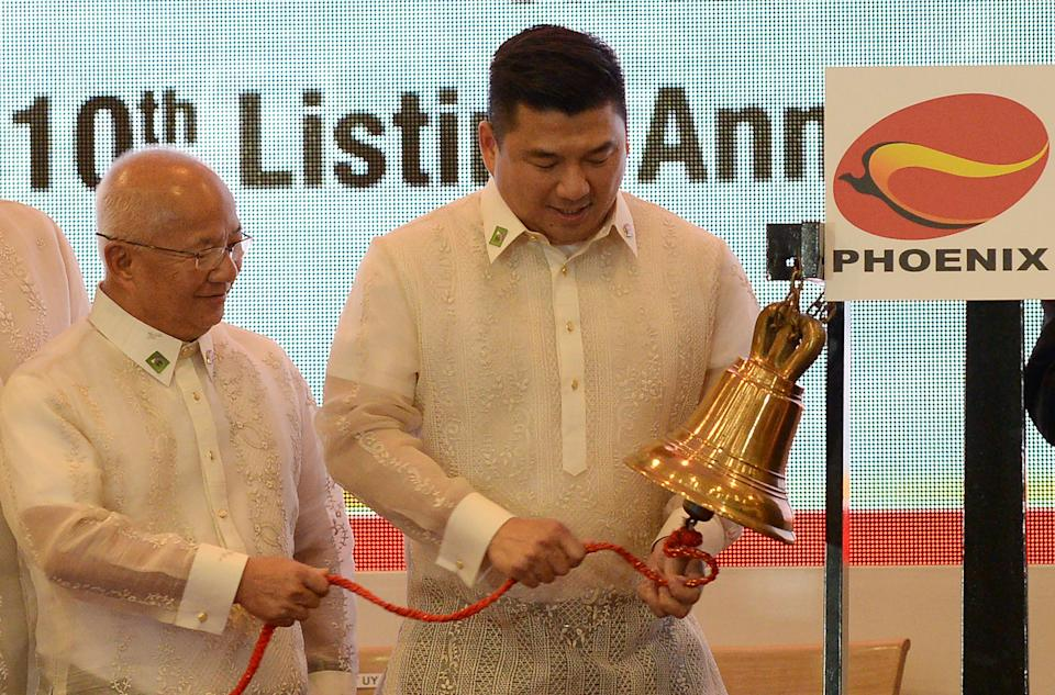 Dennis Uy (R), chairman and executive officer, and Domingo Uy (L), chairman of the board of Philippines' Phoenix petroleum company, ring the bell at the Philippine Stock Exchange in the financial district of Makati, suburban Manila on July 11, 2017, on the company's tenth anniversary of its listing. / AFP PHOTO / TED ALJIBE (Photo credit should read TED ALJIBE/AFP via Getty Images)