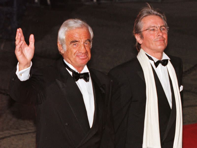 """FILE PHOTO: French actors Jean-Paul Belmondo and Alain Delon pose for photographers as they arrive at Berlin's theatre """"Schauspielhaus\"""