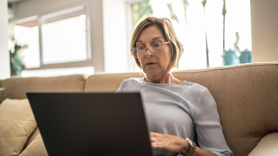 Mature woman using laptop in the living room.