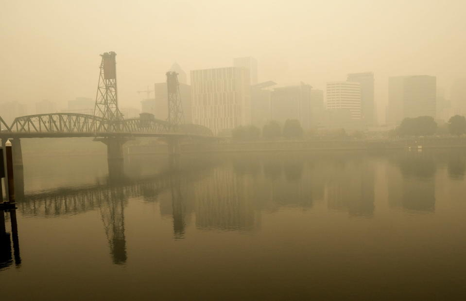 In this photo provided by Don Ryan, heavy smoke from wildfires envelops the Willamette Bridge and downtown Portland, Ore., Wednesday, Sept. 16, 2020. Dangerously dirty air spewing from the West Coast wildfires is seeping into homes and businesses, sneaking into cars through air conditioning vents and preventing people already shut away by the coronavirus pandemic from enjoying a walk or trip to the park. (Don Ryan via AP)