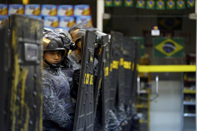 A policeman peers behind his riot shield inside Ana Rosa subway station during the fifth day of metro worker's protest in Sao Paulo June 9, 2014. A court set a 500,000 reais penalty ($223,000) for each day they stay off work from Monday and also declared the strike illegal, complicating preparations for the World Cup opening match. REUTERS/Kai Pfaffenbach (BRAZIL - Tags: BUSINESS EMPLOYMENT SOCCER SPORT TRANSPORT CIVIL UNREST WORLD CUP)