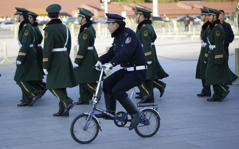 Chinese paramilitary policemen march as police officer rides a bicycle during the 18th Chinese Communist Party Congress in Tiananmen Square in Beijing, China, Tuesday, Nov. 13, 2012. (AP Photo/Lee Jin-man)
