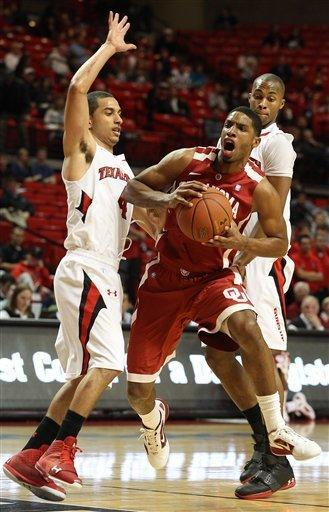 Oklahoma's Cameron Clark, center, drives between Texas Tech's Ty Nurse (4) and Jaye Crockett, right, during their NCAA college basketball game in Lubbock, Texas, Saturday, Feb. 11, 2012. (AP Photo/Lubbock Avalanche-Journal, Zach Long) ALL LOCAL TV OUT