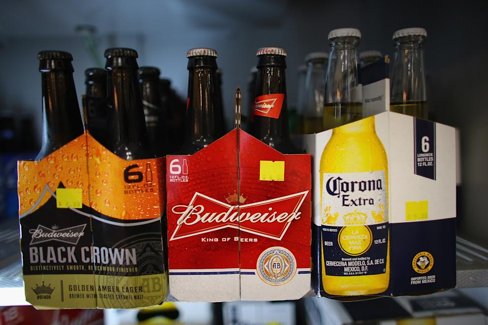 MIAMI, FL - JANUARY 31:  Six packs of Anheuser-Busch's Budweiser and Grupo Modelo's Corona Extra beers sit on a shelf at the Chandi Wine and spirits store on January 31, 2013 in Miami, Florida. Federal authorities filed a lawsuit January 31, to stop the Anheuser-Busch InBev's $20.1 billion takeover of Grupo Modelo.  (Photo  by Joe Raedle/Getty Images)