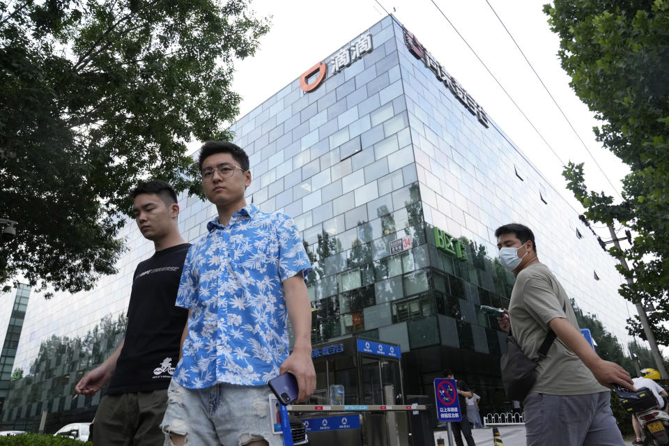 Workers pass by the Didi headquarters in Beijing Friday, July 16, 2021. Didi Global Inc. on Friday, July 30, 2021 denied a report by The Wall Street Journal that the ride-hailing service was considering buying back its U.S.-traded shares after its June market debut was disrupted by Chinese government orders to overhaul data security. (AP Photo/Ng Han Guan)