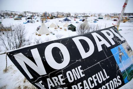 FILE PHOTO - A banner flies in the Dakota Access Pipeline protest camp near Cannon Ball, North Dakota, U.S. on January 24, 2017. REUTERS/Terray Sylvester/File Photo
