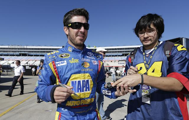 Driver Martin Truex Jr., left, finishes up signing an autograph for Brad Sigley during practice for Sunday's NASCAR Sprint Cup series auto race at the Texas Motor Speedway in Fort Worth, Texas, Friday, Nov. 1, 2013. Truex has a new full-time ride, agreeing to a multiyear deal to drive for Furniture Row Racing. (AP Photo/LM Otero)