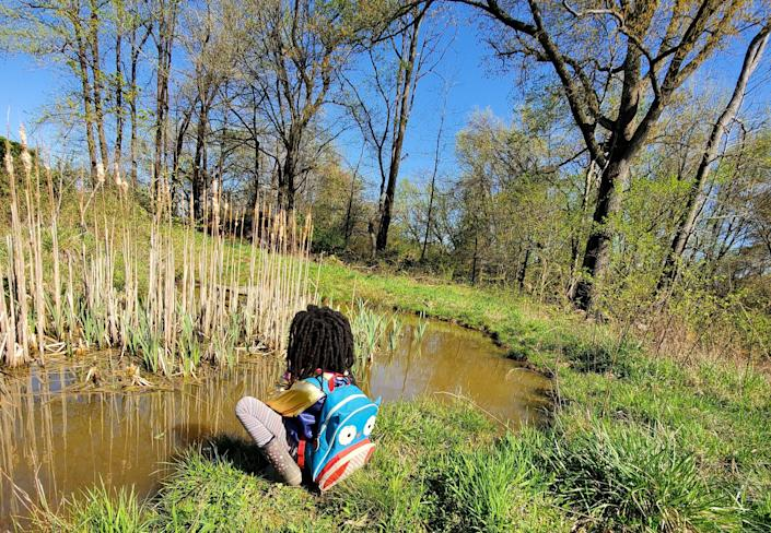 A child sits next to a pond filled with wildlife at BLISS Meadows in Baltimore. (Photo: Atiya Wells)