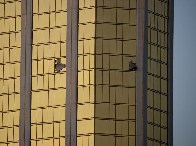 <p>Drapes billow out of broken windows at the Mandalay Bay resort and casino on the Las Vegas Strip, following a mass shooting at a music festival in Las Vegas, Nev., on Oct. 2m 2017. From two broken-out windows of the resort, Stephen Craig Paddock had an unobstructed view to rain automatic gunfire on the crowd, with few places for them to hide. Sunday night's bloodbath left dozens of people dead and hundreds wounded. (Photo: John Locher/AP) </p>