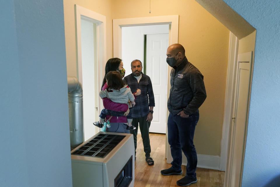 Thuy Do, left, and her husband, Jesse Robbins, right, talk with Abdul, center, Monday, Sept. 20, 2021, about a minor plumbing issue in the vacant rental home owned by the couple that they have provided Abdul — who worked as a mechanic before leaving Kabul, Afghanistan about a month ago — as a place to live with his family until they can find more permanent housing. Do was nine years old when her family arrived in the United States from Vietnam in the 1980s, and that memory led Do and Robbins to reach out to assist Afghans fleeing their country. (AP Photo/Ted S. Warren)