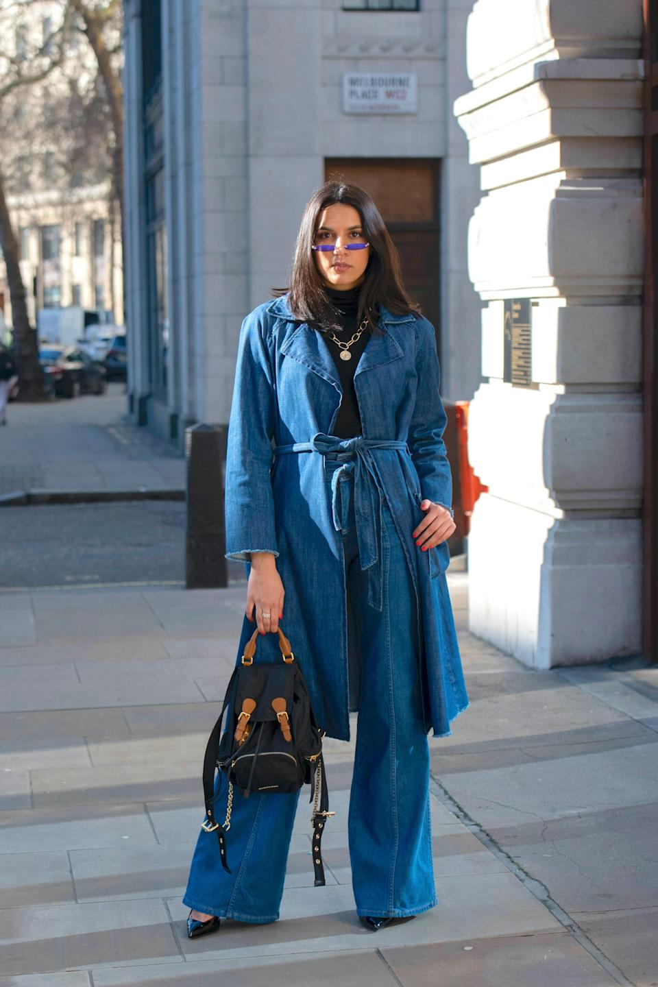 A belted denim trench and wide-leg jeans have a distinct '70s vibe, especially paired with a turtleneck and gold pendant.