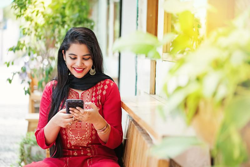 Pretty young indian woman using her phone and looking at camera (Photo: LiudmylaSupynska via Getty Images)