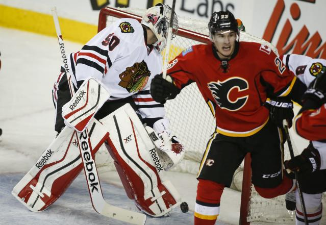 Chicago Blackhawks' goalie Corey Crawford, left, sweeps the puck out of the net as Calgary Flames' Sean Monahan celebrates his team's winning goal during overtime NHL hockey action in Calgary, Alberta, Tuesday, Jan. 28, 2014. The Calgary Flames beat the Chicago Blackhawks 5-4 in overtime. (AP Photo/The Canadian Press, Jeff McIntosh)