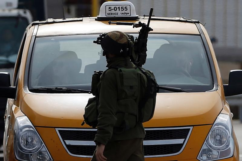An Israeli soldier checks the vehicles of Palestinians on their way out of the West Bank village of Ein Sinya, northern Ramallah on February 1, 2016