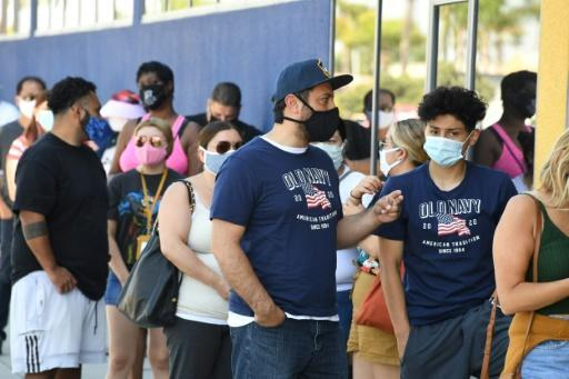 People wearing face masks wait in line to shop at an Ikea store in Carson, California on July 4, 2020