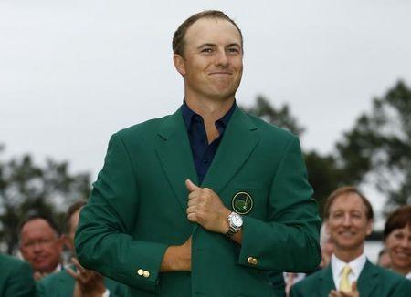 Jordan Spieth of the U.S. smiles as he wears his Champion's green jacket on the putting green after winning the Masters golf tournament at the Augusta National Golf Course in Augusta, Georgia April 12, 2015. REUTERS/Brian Snyder