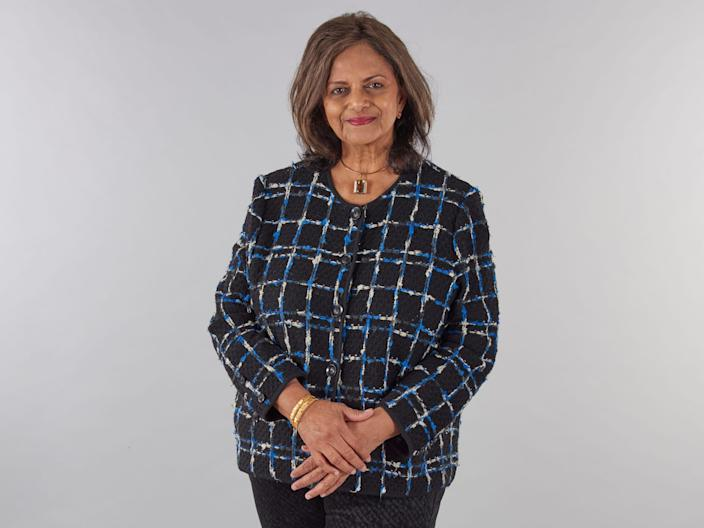 Dr. Gowri Motha stands smiling with her arms lightly crossed.