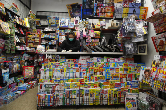 In this photo taken on Thursday, March 12, 2020, a shopkeeper wears a mask as she works in a bookshop in Codogno, Italy. The northern Italian town that recorded Italy's first coronavirus infection has offered a virtuous example to fellow Italians, now facing an unprecedented nationwide lockdown, that by staying home, trends can reverse. Infections of the new virus have not stopped in Codogno, which still has registered the most of any of the 10 Lombardy towns Italy's original red zone, but they have slowed. For most people, the new coronavirus causes only mild or moderate symptoms. For some it can cause more severe illness. (AP Photo/Antonio Calanni)
