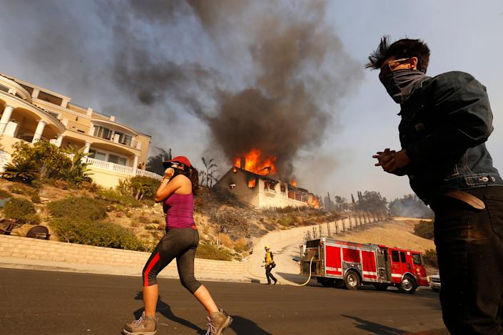 Amanda Leon and her husband, Johnny Leon, watch as firefighters fight to save homes in Ventura County.