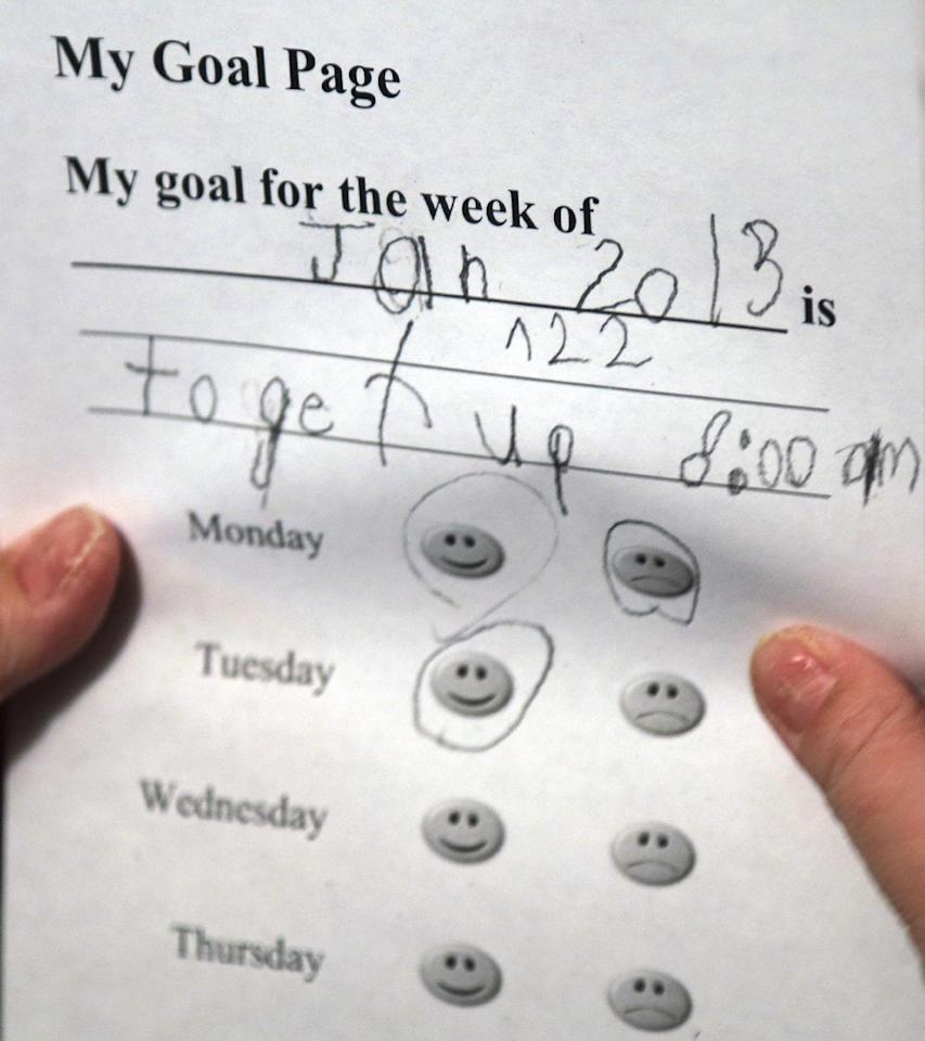 In this Tuesday, Jan. 22, 2013 photo, Devon Carrow looks at his weekly goals while attending school from home while operating a robot in the classroom, in Orchard Park N.Y. Carrow's life-threatening allergies don't allow him to go to school. But the 4-foot-tall robot with a wireless video hookup gives him the school experience remotely, allowing him to participate in class, stroll through the hallways, hang out at recess and even take to the auditorium stage when there's a show. (AP Photo/David Duprey)