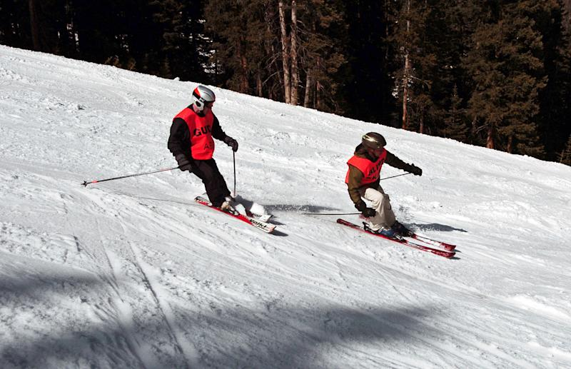 In this photo taken March 29, 2013, blind skier Wally Mozdzierz, right, skis at Colorado's Winter Park resort with his guide, Joe Ferrick, following close behind. The American Blind Skiing Foundation, a Chicago-based nonprofit, brought Mozdzierz and others to Winter Park and plans another trip to Steamboat Springs this season..(AP Photo/Thomas Peipert)