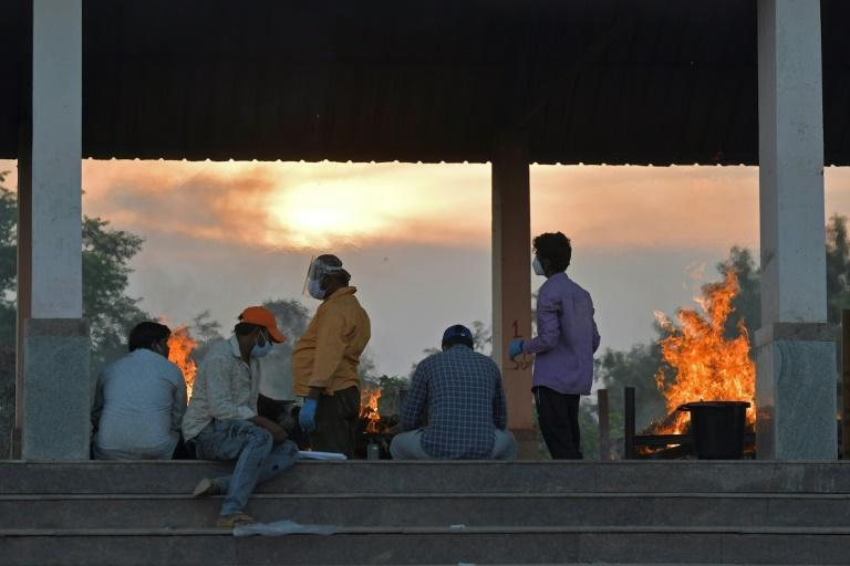 People are seen next to burning pyres of victims who lost their lives due to the coronavirus at an open crematorium in Bangalore on April 26, 2021