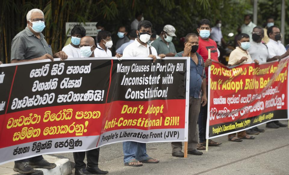 Nearly two dozen protestors belonging to the People's Liberation Front display banners against the Chinese built port city project in Colombo, Sri Lanka, Wednesday, May 19, 2021. Sri Lanka's top court has ruled that some provisions of legislation to set up a powerful economic commission in a Chinese-built port city violate the constitution and require approval by a public referendum to become law. (AP Photo/Eranga Jayawardena)