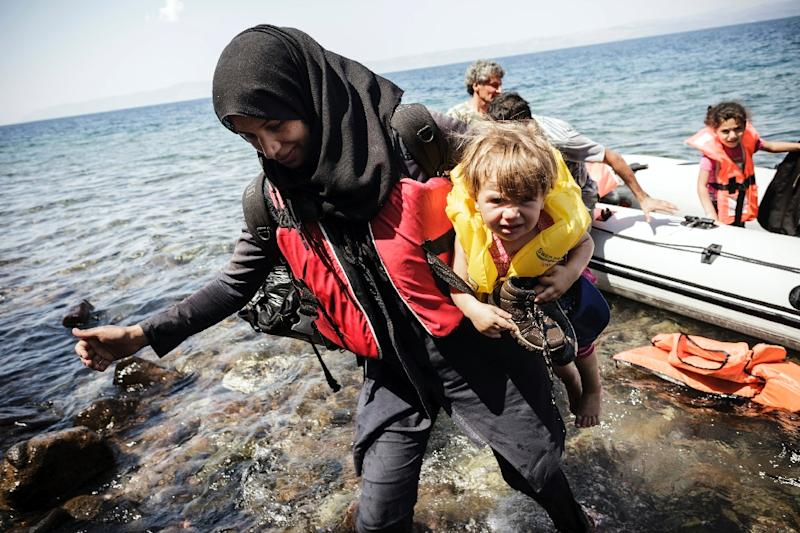 A Syrian woman carries her baby after arriving on the Greek island of Lesbos after crossing the Aegean sea in an inflatable boat from Turkey on August 20, 2015 (AFP Photo/Achilleas Zavallis)
