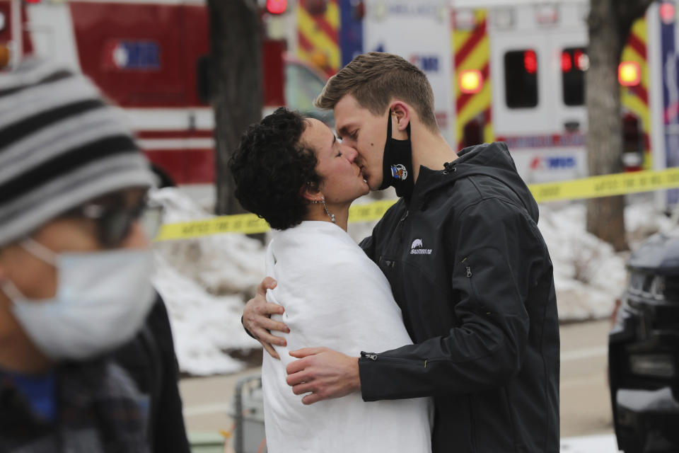 A couple kiss in the wake of a mass shooting at a King Soopers supermarket in Boulder.