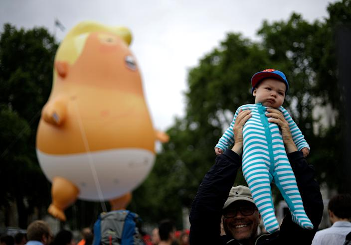"A real baby nearby the ""Trump Baby"" blimp in Parliament Square. (Photo: Matt Dunham/AP)"