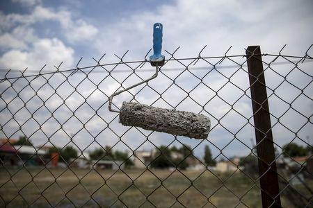 A paint roller is seen attached to a fence in the town of Elefsina, near Athens, Greece June 30, 2015. REUTERS/Marko Djurica