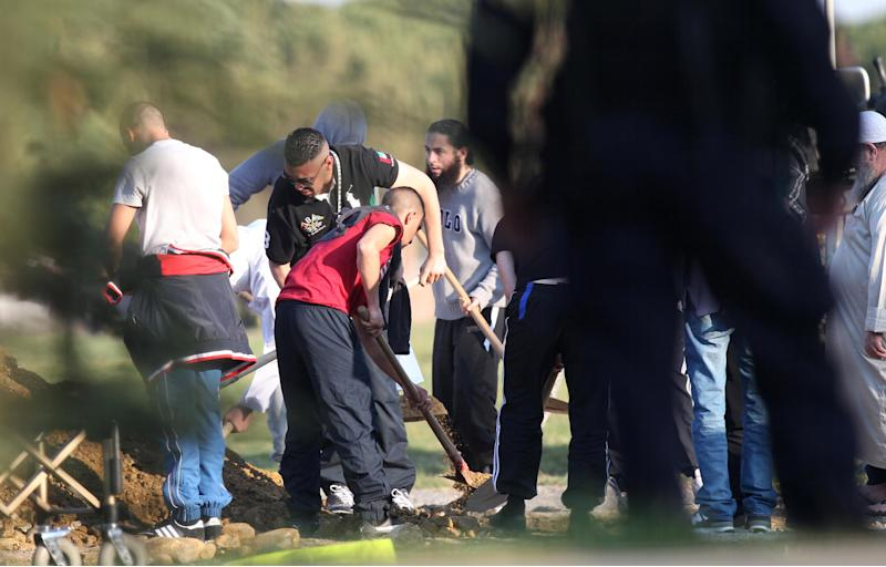 Relatives use shovels after Mohamed Merah's funeral in a cemetery near Toulouse, southern France, Thursday, March 29, 2012. Mohamed Merah is blamed for a series of deadly shootings which have shocked France and upended the country's presidential race. Merah, who claimed allegiance to al-Qaida, died in a hail of gunfire one week ago after a dramatic 32-hour-long standoff with law enforcement. Algerian authorities said they didn't want to take Merah's remains, as his Algerian-born father had wanted. (AP Photo/Marthial Roland)