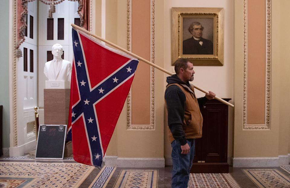 A supporter of Trump holds a Confederate flag outside the Senate Chamber during a protest after breaching the U.S. Capitol on January 6. (Photo: SAUL LOEB via Getty Images)