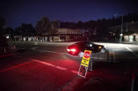 A car drives through a darkened Montclair Village as Pacific Gas & Electric power shutdowns continue in Oakland, Calif. The area remains without power after the utility cut service hoping to prevent wildfires during dry, windy conditions. (AP Photo/Noah Berger)