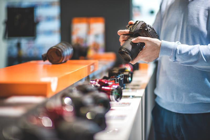 Unrecognizable male customer is holding black DSLR camera in the store. Row of other camera models is visible on the shelf.