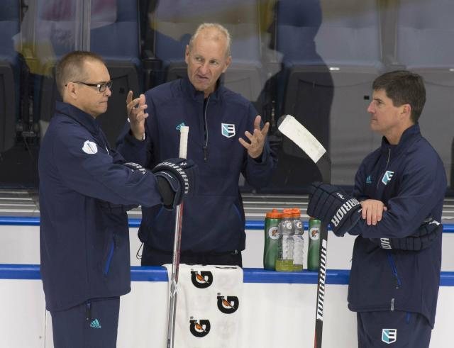 FILE - In this Sept. 5, 2016, file photo ,Team Europe head coach Ralph Krueger, center, chats with assistant coaches Paul Maurice, left, and Brad Shaw during practice in preparation for the World Cup of Hockey tournament at the Videotron Centre in Quebec City. Coaches who have worked closely with Krueger over the years are glad hes back as a part of their fraternity after five years as chairman of English Premier League soccer club Southampton FC. The Buffalo Sabres recently hired Krueger as their new coach. (Jacques Boissinot/The Canadian Press via AP, File)
