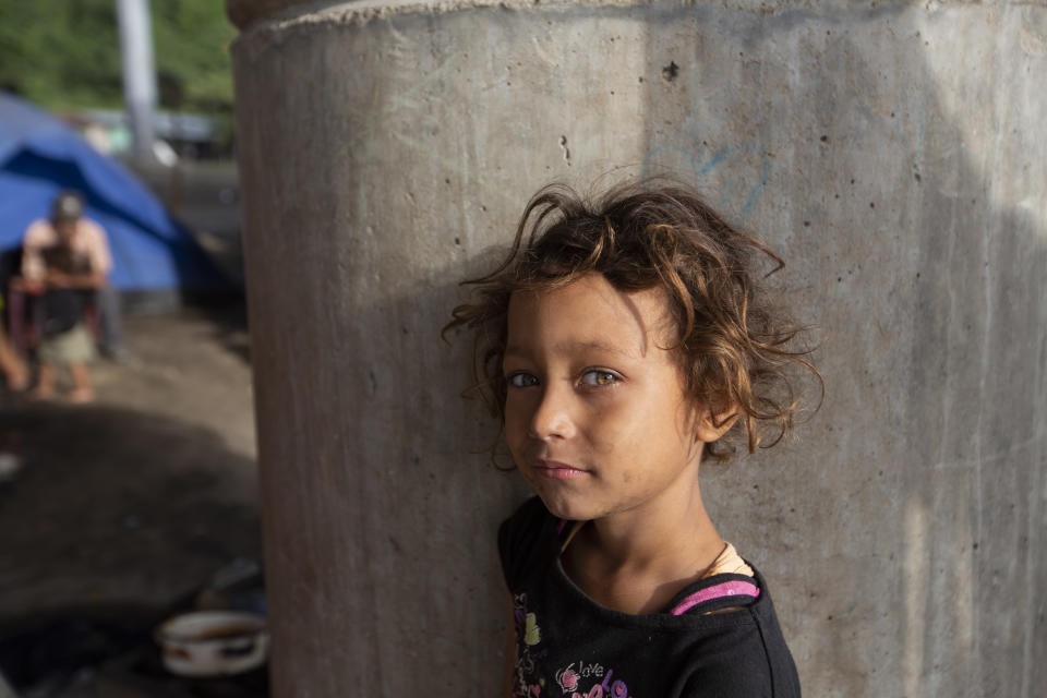 Katerine waits for breakfast cooked by her family under a bridge on the outskirts of San Pedro Sula, Honduras, Monday, Jan. 11, 2021. The 9-year-old has lived under this bridge with her family since they lost their home to last year's hurricanes Eta and Iota in November. (AP Photo/Moises Castillo)