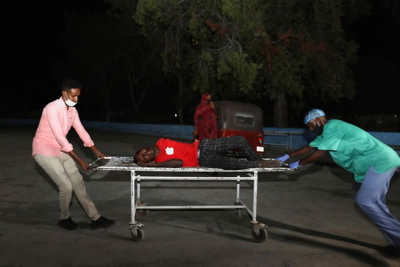 People assist an injured person outside Madina Hospital after a blast Luul Yemeni restaurant near the port in Mogadishu