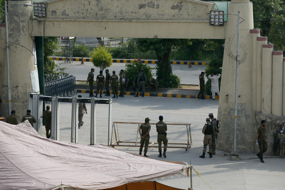 Pakistan's army and police officers stand at the one of the entry point of the Pindi Cricket Stadium before the stat of the first one day international cricket match between Pakistan and New Zealand at the Pindi Cricket Stadium, in Rawalpindi, Pakistan, Friday, Sept. 17, 2021. The limited-overs series between Pakistan and New Zealand has been postponed due to security concerns of the Kiwis. (AP Photo/Anjum Naveed)