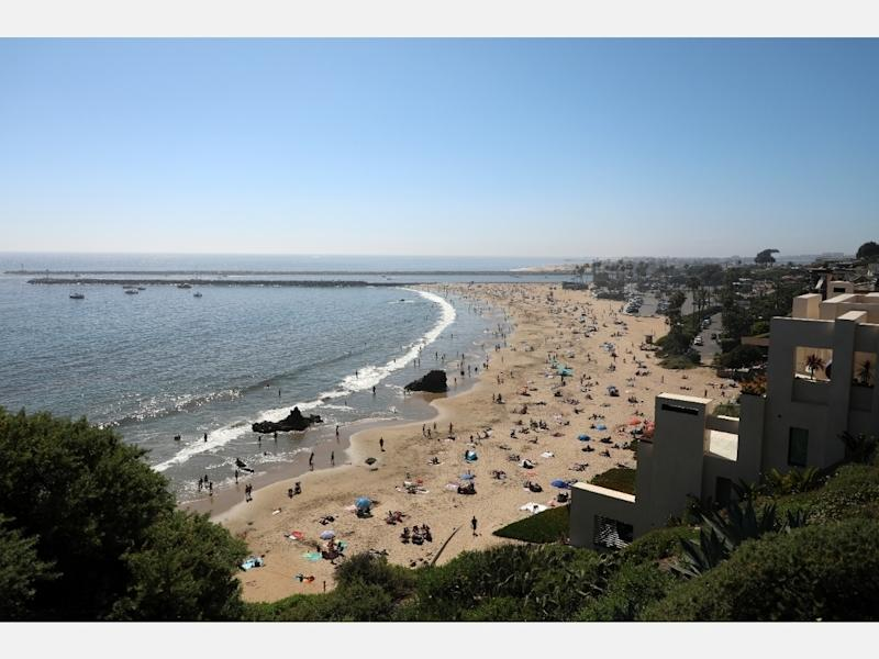 People are seen gathering on the Corona del Mar State Beach on April 25, 2020 in Newport Beach, California. Southern California is expecting summer like weather this weekend as social distancing and beach closures in neighboring counties continue.