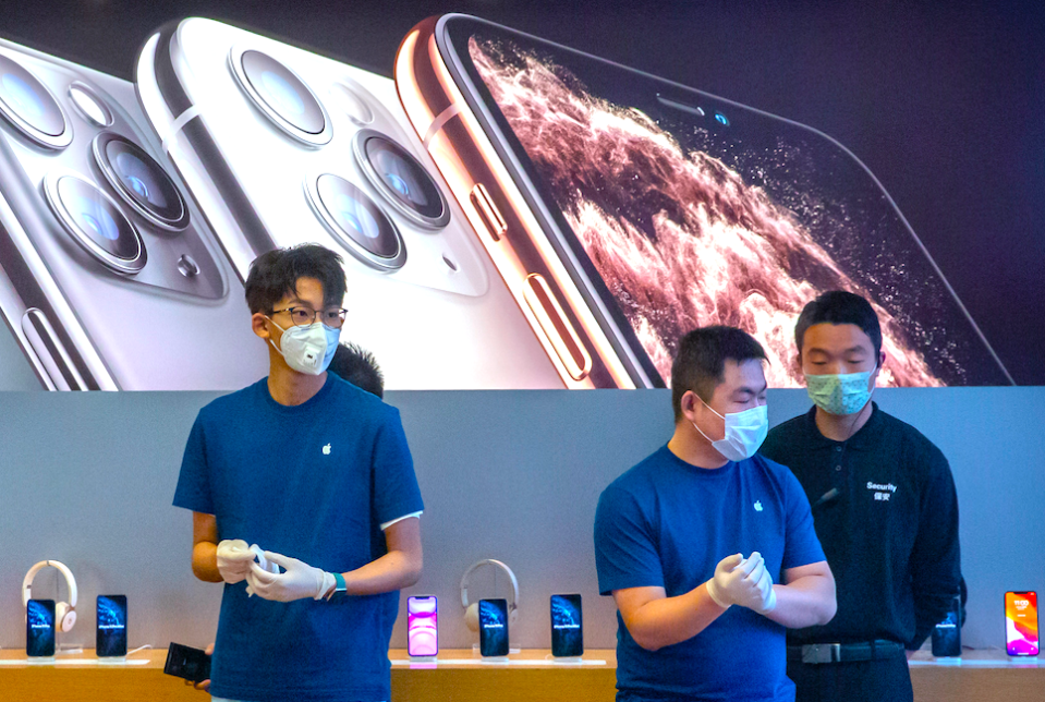 Employees wear face masks as they stand in a reopened Apple Store in Beijing, Friday, Feb. 14, 2020. (AP Photo/Mark Schiefelbein)