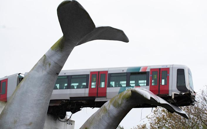 The whale's tail of a sculpture caught the front carriage of a metro train as it rammed through the end of an elevated section of rails - AP